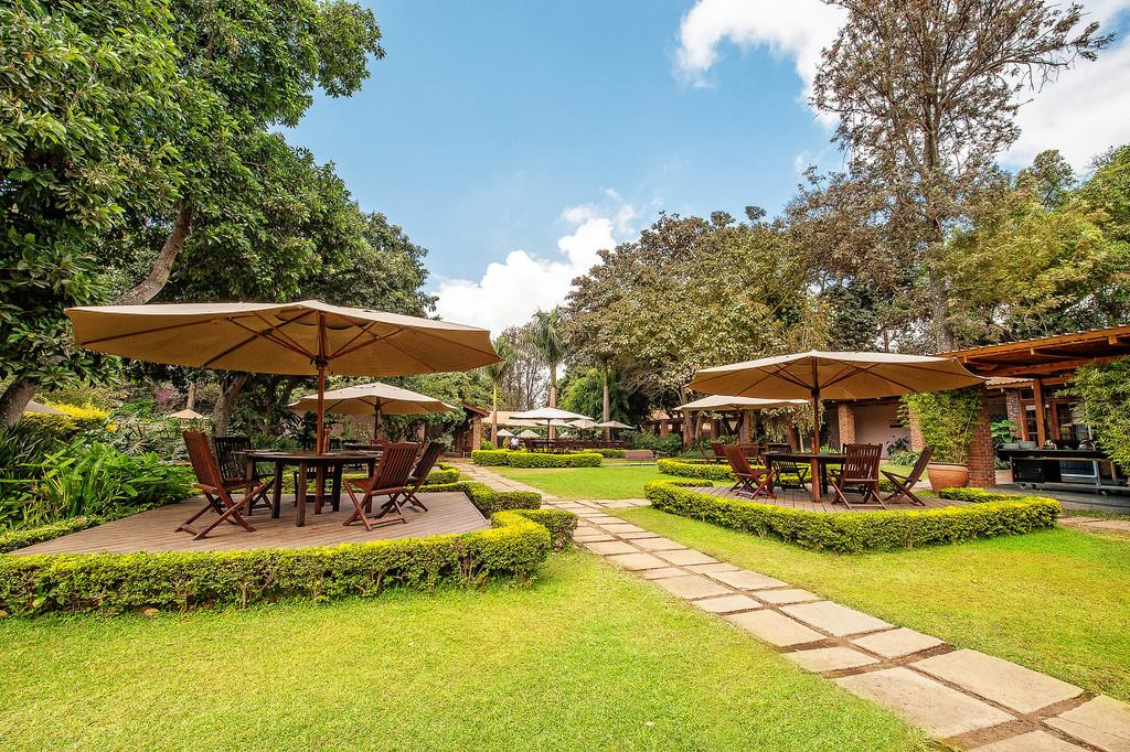 Garten der Arusha Coffee Lodge in Tansania | Abendsonne Afrika