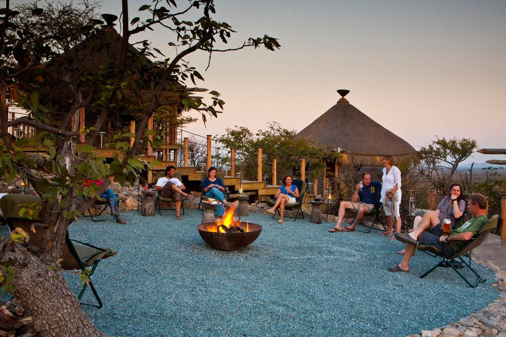 Gemütliche Runde um die Feuerstelle des Dolomite Camps im Etosha Nationalpark in Namibia | Abendsonne Afrika