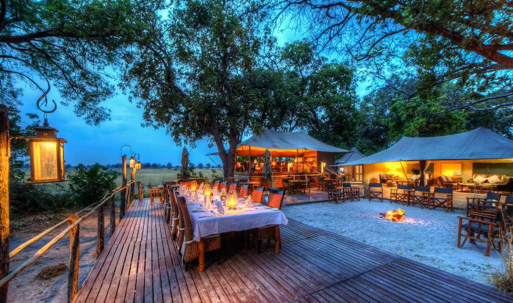 Beleuchteter Hauptbereich des Kadizora Camps in Botswana | Abendsonne Afrika