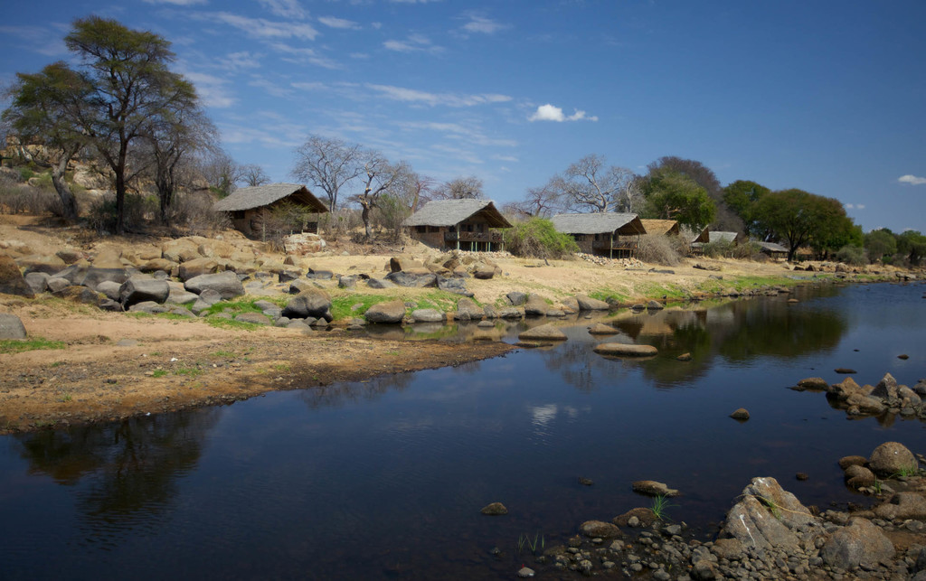 Blick vom Fluss auf die Ruaha River Lodge in Tansania | Abendsonne Afrika