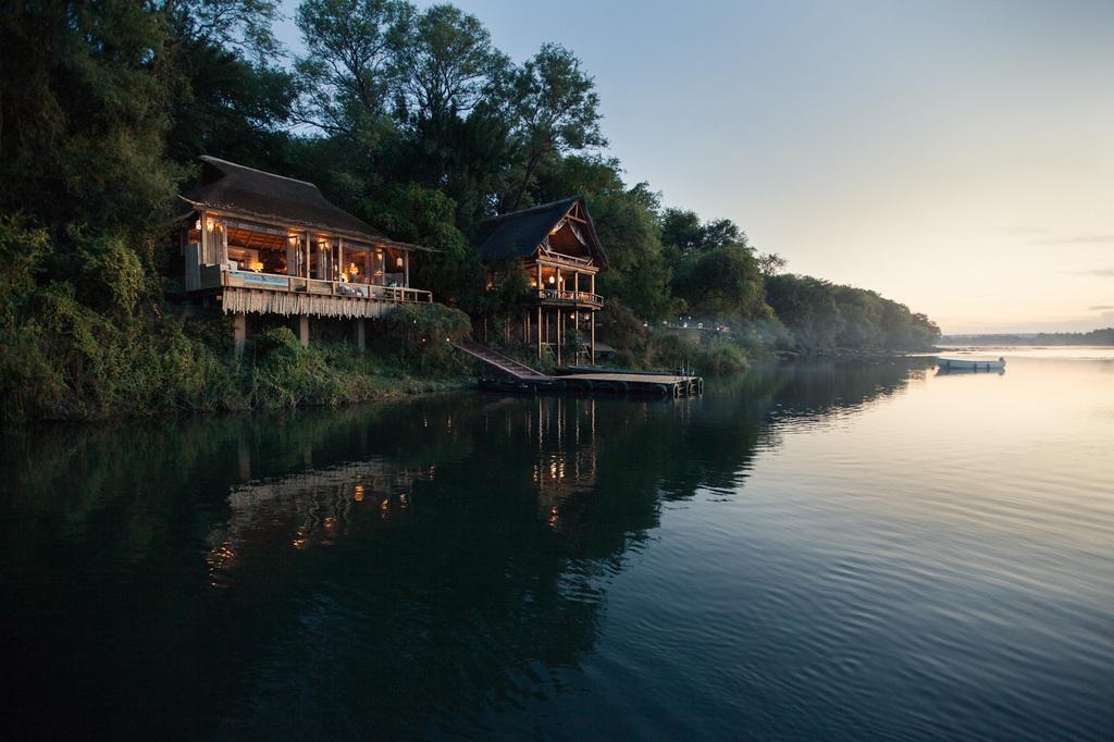 Blick vom Wasser auf die Tongabezi Lodge in Sambia | Abendsonne Afrika