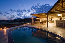 Pool bei Nacht des Damaraland Camp in Namibia | Abendsonne Afrika
