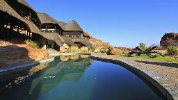 Pool und Haupthaus der Twyfelfontein Country Lodge in Namibia | Abendsonne Afrika