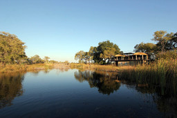 Blick vom Fluss auf die Nkasa Lupala Tented Lodge in der Caprivi Region in Namibia | Abendsonne Afrika